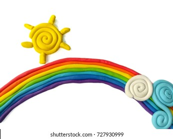 Clay plasticine made are beautiful rainbow ,yellow sun with cloud (blue and white)  placed on white background,colorful dough