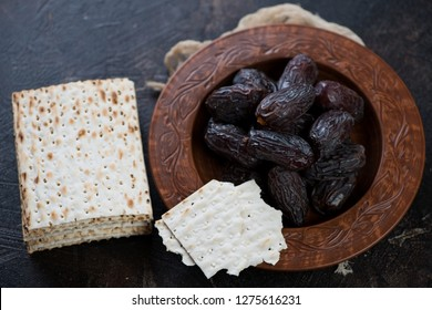 Clay plate with date fruits and matzo bread on a dark brown stone background