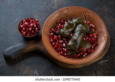 Clay plate with dolma or dolmades and pomegranate seeds on a dark brown stone background, studio shot