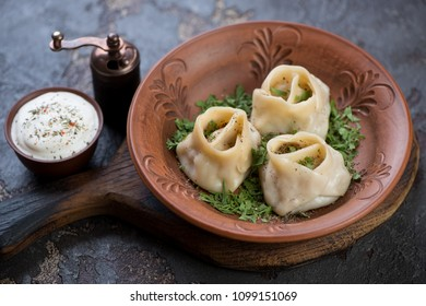 Clay plate with manti or steamed meat dumplings, greens and sour cream, studio shot, selective focus