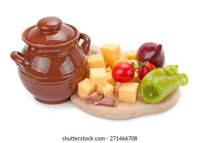 clay pot, cheese and vegetables on wooden board on white background
