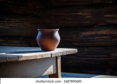 Clay pot (clay pottery) on an old wooden table in an old rustic house. Pottery and peasant life. Still life with pottery.