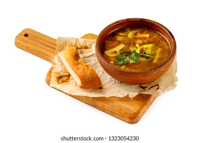 Clay pot of shchi soup with cabbage and mushrooms served with a slice of bread at wooden tray isolated at white background.