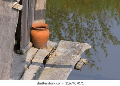 Clay pot stands on wooden pier on the water