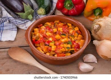 Grano de arcilla con ratatouille vegetal y salsa de tomate, sobre una mesa rústica de madera