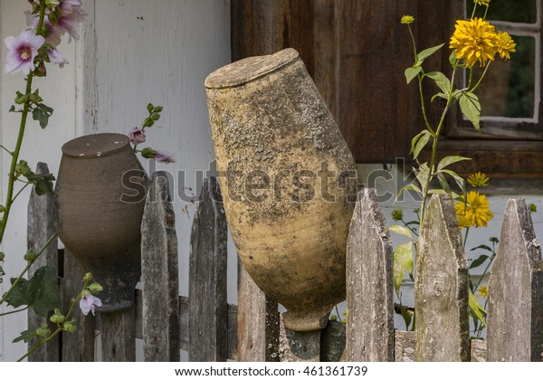 Clay pots hanging to dry on a rustic wooden fence