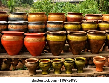 Clay pots stacked for sale on African roads. Pottery making place. Local craft market in Africa. Unique handmade colorful ceramic pots. Craftsmanship. African style.