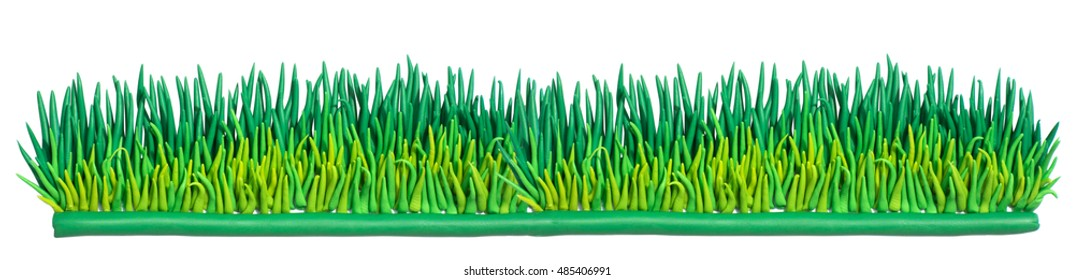 Clay putty, plasticine handmade green grass. Isolated grass strip on white background.