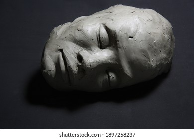 clay sculpture, with closed eyes. face with shadows, lying on black floor