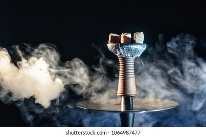 Clay shisha bowl with craft flawoured tobacco and red hot coconut coil with hookah smoke black background isolated. Smoking hookah at party concept
