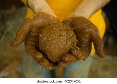 Clay and Straw ball. Close-up of hands holding a ball made of clay and straw for permaculture natural building
