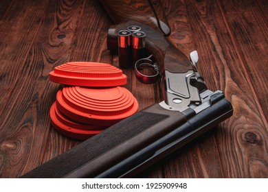 Clay target plates for shooting with rifle on wooden background.