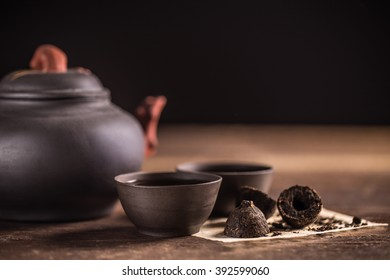 Clay teapot and two small cups full of hot pu-erh tea