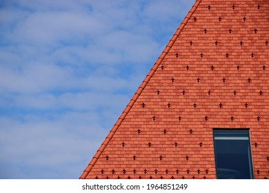 clay tile roof. steep slope in red brown color. bright blue sky wand white clouds. roof window or skylight. metal ice and snow guard in square pattern. modern new construction concept. snow breaker