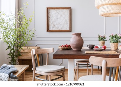 Clay vase on the table in a dining room interior with a plant, chairs and art on a wall