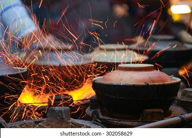 Claypot meal preparation using charcoal fire.
