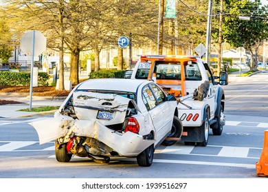 Clayton, North Carolina USA-03 19 2021: A Car is Towed Away by a Tow Truck After a Serious Rear End Collision.