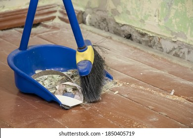 Clean up after repairs. Sweep up construction debris with a brush in a dustpan. Sweeping at home. Tools for cleaning the house. Make home repairs. The dust and debris after the renovation.