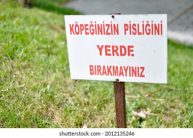 Clean Up After Your Dog sign in Turkish at the park.