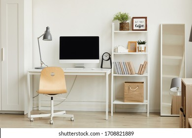 Clean background image of minimalistic apartment interior with focus on computer desk against white wall, copy space