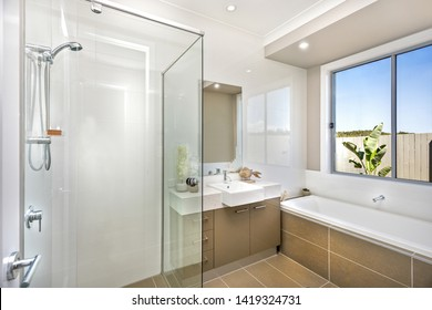 Clean bathroom featuring a glass shower area, a basin with cabinets, and a bathtub