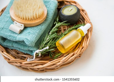 Clean beauty. Natural spa products with rosemary herb and oil, candle, towel and brush, natural home skincare products, homespa and wellness clean beauty products