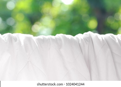 Clean bed sheet hanging on clothesline at backyard.White and soft bedding sheet against green bokeh of tree in the outside garden.Concept of Allergy prevention and hygiene sleeping ware.