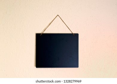 A clean blank black chalkboard hanging on a wall  with rope indoors with copy space.