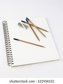 Clean blank pad of paper with pencil on white  with assorted pencils and eraser overhead view