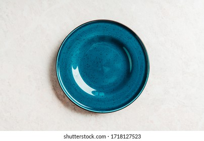 Clean blue plate on the rustic background. Selective focus. Shot from above.