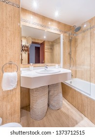 Clean bright bathroom interior with a big mirror,bathtub,white sink and marble tiles. Original designed hotel space with modern pieces