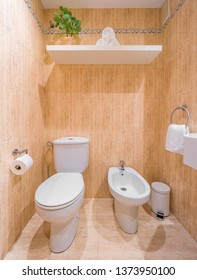 Clean bright bathroom interior with white toilet and marble tiles. Original designed hotel space with modern pieces