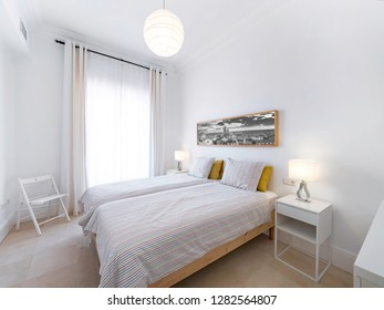 Clean bright bedroom with bed, duvet,side tables, lamps, photography. Minimalist white stylish interior