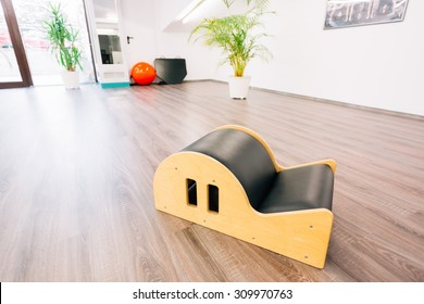 Clean and bright pilates room with close-up on small barrel.
