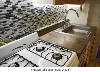 A clean and bright small kitchen in an apartment with concrete countertop and tile backsplash