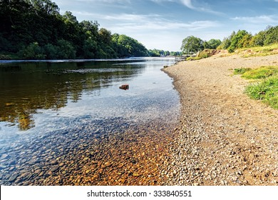 Clean, clear waters of the River Trent. Nottinghamshire, flows between a wooded bank and a sandstone beach under a blue sky