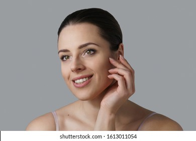 Clean close up portrait of a young brunette smiling and slightly touching her cheek with fingers