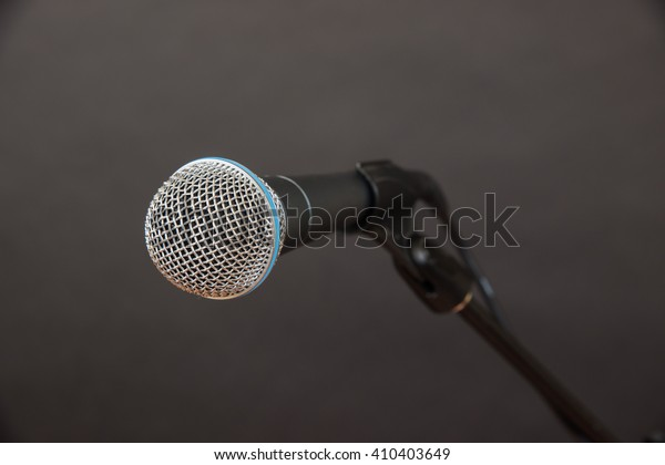Clean, close-up shot of a dynamic microphone (mic) ready to be used.
