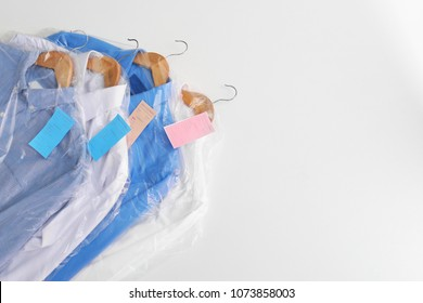 Clean clothes after dry-cleaning on white background