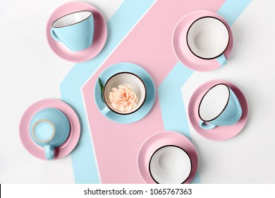 Clean coffee or tea set. Plenty of elegant porcelain light blue and pastel pink cups and at funky abstract background, top view and flat lay.
