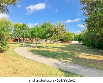 Clean concrete pathway surrounded with oak trees and grass lawn at neighborhood park near Dallas, Texas, America. Residential houses with wooden fences in the distance