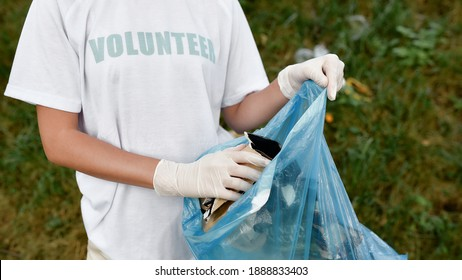 Clean up day. Cropped shot of a young woman volunteer wearing uniform and rubber gloves with trash bag in hands cleaning forest or park from garbage. Ecology problems and nature pollution