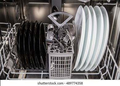 Clean dishes after washing in modern dishwasher machine
