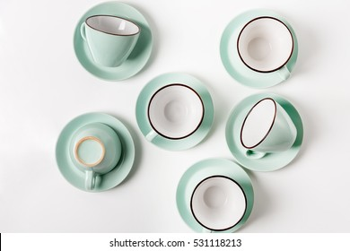 Clean dishes, coffee or tea set. Plenty of elegant porcelain light blue cups and saucers at white background, high key, top view and flat lay.