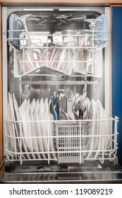 Clean dishes from dishwasher with hot steam around.