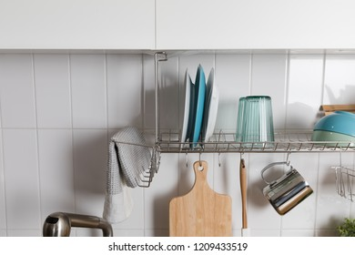 Clean dishes drying on metal dish rack on light background. Kitchen utensils and dishware on wooden shelf. Kitchen interior background.Text space.