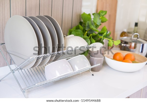 Clean dishes drying on metal dish rack on shelf