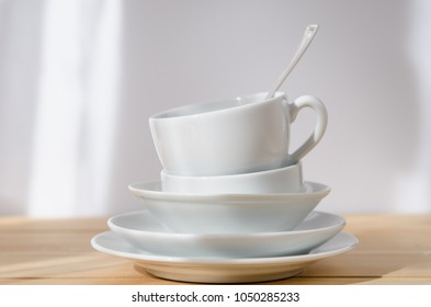 clean dishes - plate, saucer, cup, spoon, on white background on a wooden table