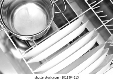clean dishes and a steel pot in the dishwasher basket, from above, close up