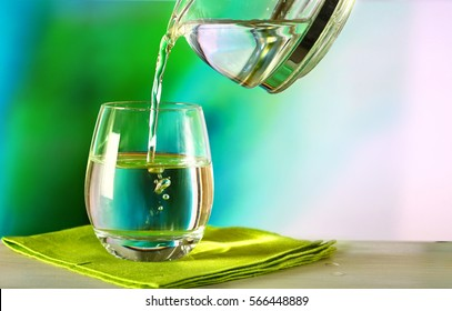 Clean drinking water is poured from a jug into a round glass cup on a wooden table and a light green napkin close-up macro on a green nature outdoors background .